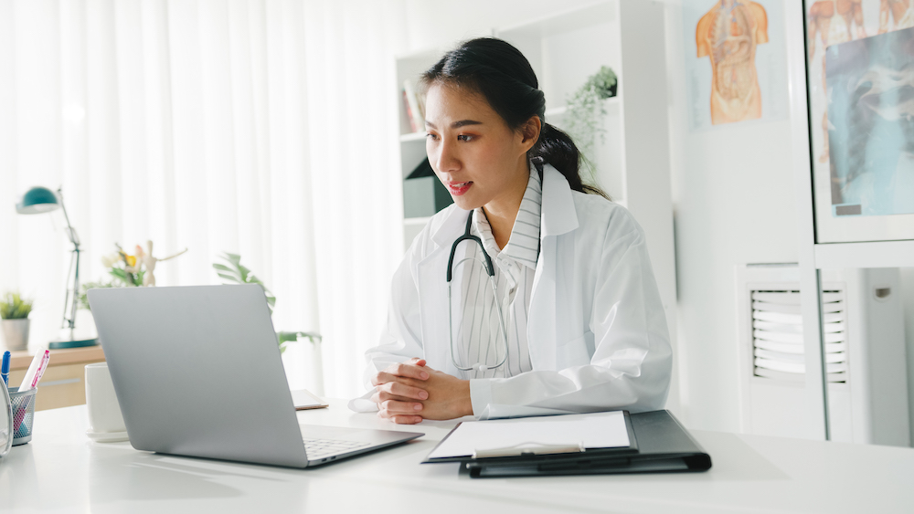 Asian female doctor using laptop for telehealth appointment
